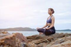 Le coucher du soleil de pratique de yoga de femme sur la plage Photos libres de droits