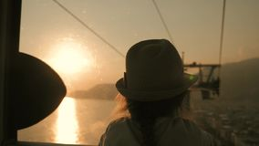 Le coucher du soleil de touristes d'ascenseur de câble de fille de silhouette, abaissent, apprécient la vue de la mer et des mont clips vidéos
