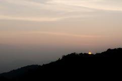 Le coucher du soleil derrière la montagne Photographie stock