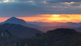 Le coucher du soleil dramatique rayonne derrière la silhouette de la montagne Images libres de droits