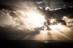 Le coucher du soleil dramatique rayonne par un ciel foncé nuageux au-dessus de l'océan Photographie stock libre de droits