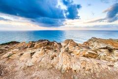 Le coucher du soleil dramatique rayonne par un ciel foncé nuageux au-dessus de l'océan Photo libre de droits
