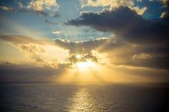 Le coucher du soleil dramatique rayonne par un ciel foncé nuageux au-dessus de l'océan Photo stock
