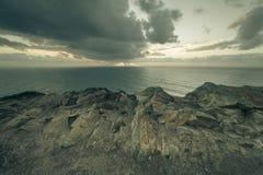 Le coucher du soleil dramatique rayonne par un ciel foncé nuageux au-dessus de l'océan Image stock