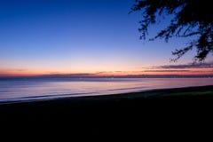 Le coucher du soleil en mer avec des arbres balancent à la plage Chanthabur de Chaolao Tosang photos libres de droits