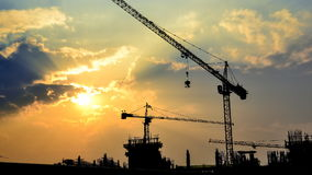 Le coucher du soleil et la silhouette de laps de temps tendent le cou dans le chantier de construction