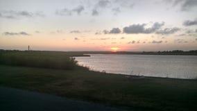 Le coucher du soleil et le phare image stock