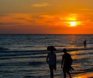 Le coucher du soleil magnifique derrière la silhouette des amateurs de plage aux roches indiennes échouent sur le Golfe du Mexiqu photos stock