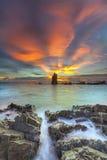 Le coucher du soleil ondule la ligne de mèche roche d'impact sur la plage Images libres de droits