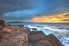 Le coucher du soleil ondule la ligne de mèche roche d'impact sur la plage Image stock