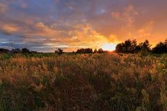Le coucher du soleil opacifie la pluie ensuite au-dessus du champ photographie stock