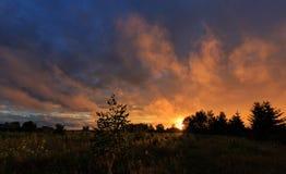 Le coucher du soleil opacifie la pluie ensuite au-dessus du champ image stock