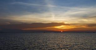 Le coucher du soleil orange au-dessus du bord de mer et le marécage avec la silhouette écossent f Image stock
