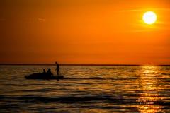Le coucher du soleil orange, les gens silhouettent avoir l'amusement photo stock