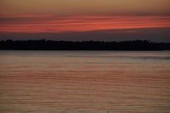 Le coucher du soleil orange rose a réfléchi sur le lac calme par la silhouette d'arbres Image stock