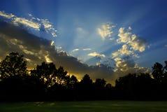 Le coucher du soleil rayonne à la maison A Images libres de droits