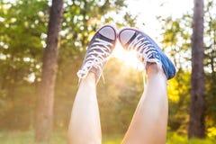 Le coucher du soleil rayonne le throug les jambes dans des espadrilles Photo libre de droits