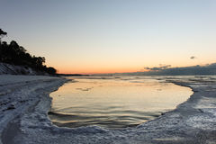 Le coucher du soleil rose de ton, la plage neigeuse et la glace ont lapidé la mer baltique Photo stock