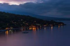 Le coucher du soleil sur la plage avec des vues des montagnes et du village de pêche Photographie stock libre de droits