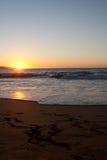 Le coucher du soleil sur la plage avec le pied estampe dans le sable Images libres de droits