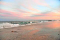 Le coucher du soleil sur la plage colore le ciel, l'eau et le sable avec une lueur chaude photos libres de droits
