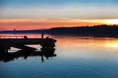 Le coucher du soleil sur la rivière, pêcheurs pêchent Image libre de droits