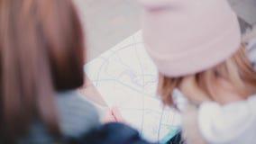 Le coup courbe de vue arrière de plan rapproché de l'homme de touristes et la femme regardant un voyage de carte de ville guident banque de vidéos