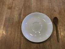 Le coup courbe du plat blanc et le thé en bois administrent à la cuillère sans compter que lui Photo libre de droits