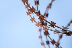 Le coupeur de bande barbelé rouillé contre le ciel bleu, se ferment  Image stock
