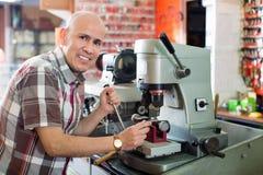 Le coupeur principal professionnel faisant la porte verrouille des copies dans le serrurier Images stock