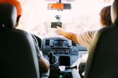 Le couple à l'intérieur de la voiture emploie le navigateur de GPS Image stock