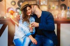 Le couple à la mode dans l'amour célèbre avec le champagne dans une barre Image libre de droits