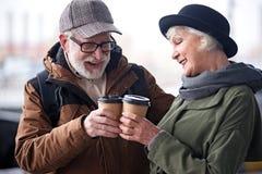 Le couple âgé heureux parle avec le sourire tout en tenant l'expresso Image stock