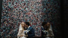 Le couple élégant affectueux des nouveaux mariés étreint tendrement au-dessus du mur coloré banque de vidéos