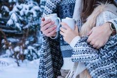 Le couple étreint et tient des tasses de café avec la guimauve Image libre de droits