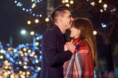 Le couple étreint la nuit dans les lumières de la ville Photo libre de droits