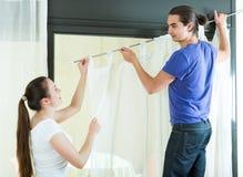 Le couple accroche des rideaux sur la fenêtre Photos libres de droits