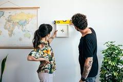 Le couple accroche la peinture de cadre sur le mur Photographie stock libre de droits