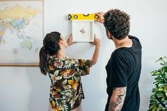 Le couple accroche la peinture de cadre sur le mur Photographie stock