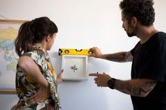 Le couple accroche la peinture de cadre sur le mur Photos stock
