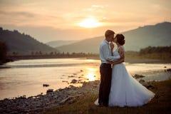 Le couple adorable de nouveaux mariés embrasse doucement sur la berge pendant le coucher du soleil photos stock