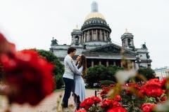 Le couple affectueux étreint sur un fond des fleurs rouges et de l'architecture de vintage image stock