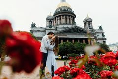 Le couple affectueux étreint sur un fond des fleurs rouges et de l'architecture de vintage photographie stock