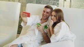 Le couple affectueux attrayant prend le selfie avec des verres de cocktail utilisant le smartphone tout en détendant dans le salo banque de vidéos