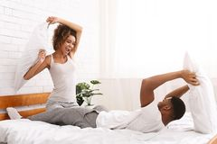Le couple affectueux gai combat par des oreillers dans le lit images stock