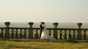 Le couple affectueux heureux des nouveaux mariés s'amuse tout en étreignant près de la barrière du vieux château au-dessus du fon banque de vidéos