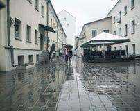 Le couple affectueux heureux est sous un parapluie sur une rue de ville un jour pluvieux Images libres de droits