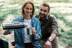 Le couple affectueux joyeux est prêt à boire la boisson chaude en nature Image stock