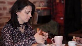 Le couple affectueux mange un croissant et un sandwich dans un café, boit du café banque de vidéos