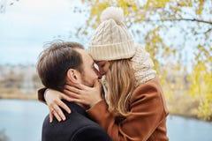 Le couple affectueux marchant en parc en automne étreint et des baisers Automne Image stock